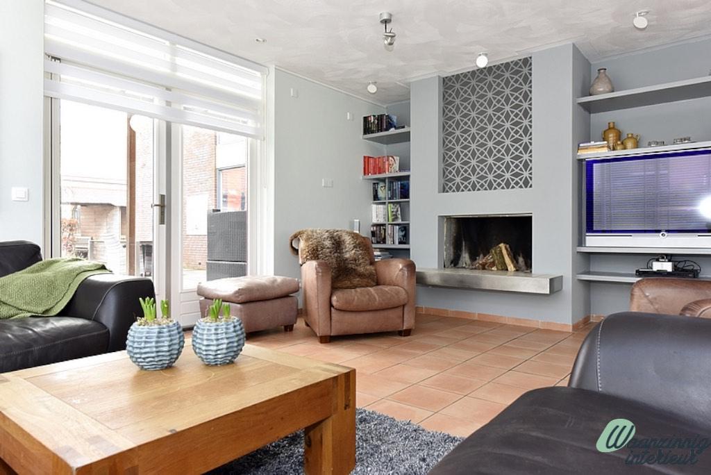 Na foto van de woonkamer restyling. Bruine meubels en grijs en groen tinten