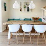 Houten eetkamertafel met witte stoelen en witte lampen daarboven. De accessoires modern groen/blauw wat helemaal bij de rest van het interieur past.